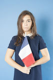 Young girl holding the French flag triumphantly. Royalty Free Stock Photo