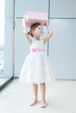 Young girl holding gift wrapped box on her head Royalty Free Stock Images