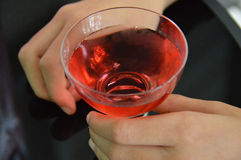 Two hands holding a non-alcoholic party cocktail against black table Stock Photos