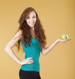 Young girl holding a green apple smiling Royalty Free Stock Photos