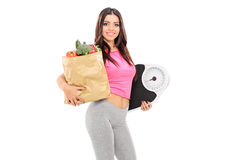 Young girl holding a grocery bag and weight scale Stock Photography