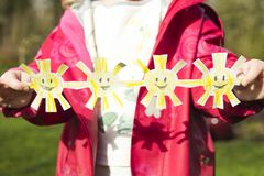 Young girl holding handicrafted paper suns on a sunny day outdoo Royalty Free Stock Photo
