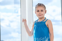 Young girl holding handle of plastic window with blue sky Stock Image