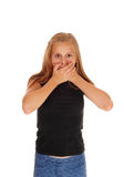 Young girl holding hands over mouth. royalty free stock photography