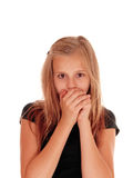 Young girl holding hands over mouth. stock image