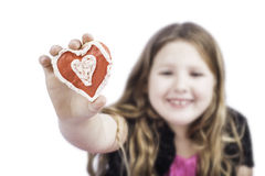Young girl holding a heart cookie Stock Photography