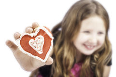 Young girl holding a heart cookie Royalty Free Stock Image
