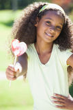 Young girl holding a heart lollipop in the park Royalty Free Stock Image