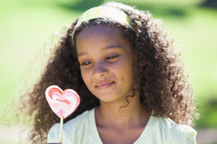 Young girl holding a heart lollipop in the park Stock Image
