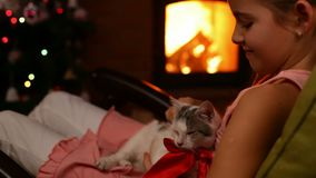 Young girl holding her christmas present by the fire - caressing a kitten stock footage