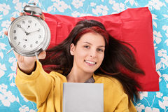 Young girl holding her favorite book and alarm clock Stock Image