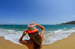 Young girl holding her hat on sandy beach Stock Photos
