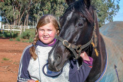 Young girl holding her horse Stock Images