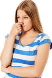 Young girl holding her nose smelling something stinking. Young girl holding her nose smelling something stinking royalty free stock images