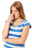 Young girl holding her nose smelling something stinking. Young girl holding her nose smelling something stinking stock image