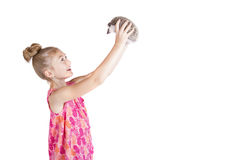A young girl holding her pet hedgehog up in the air. On an isolated white background Royalty Free Stock Photos