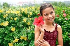 Young girl holding hibiscus stock photo