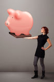 Young girl holding a huge savings piggy bank. Beautiful young girl holding a huge savings piggy bank stock photography