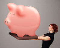 Young girl holding a huge savings piggy bank. Beautiful young girl holding a huge savings piggy bank Royalty Free Stock Image