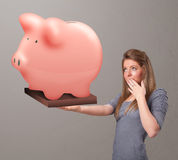 Young girl holding a huge savings piggy bank. Beautiful young girl holding a huge savings piggy bank Royalty Free Stock Photos