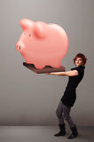 Young girl holding a huge savings piggy bank Stock Images