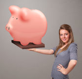 Young girl holding a huge savings piggy bank. Beautiful young girl holding a huge savings piggy bank Royalty Free Stock Photo