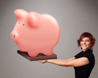 Young girl holding a huge savings piggy bank Royalty Free Stock Photo