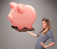 Young girl holding a huge savings piggy bank Stock Photo
