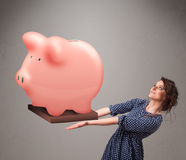 Young girl holding a huge savings piggy bank. Beautiful young girl holding a huge savings piggy bank Royalty Free Stock Images