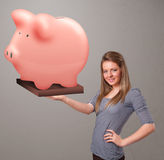 Young girl holding a huge savings piggy bank. Beautiful young girl holding a huge savings piggy bank Royalty Free Stock Photography
