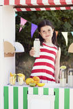 Young girl holding a juice bottle at fruit stand Stock Photo