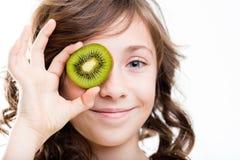 Young girl holding kiwi to eyes Stock Image