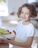 Young girl holding knife in kitchen Royalty Free Stock Images