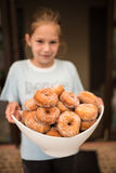 Young girl holding a large bowl full of donuts Stock Photography