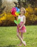 Young girl holding large Flower shaped wind wheel royalty free stock photography