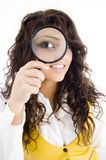 Young girl holding magnifier and showing Stock Photography