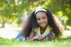 Young girl holding magnifying glass in the park smiling at camera Royalty Free Stock Photo