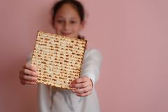 Young girl holding matzah or matza. Jewish holidays Passover invitation or greeting card.Selective focus.Copy space. royalty free stock images