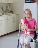Young girl holding medical skeleton Royalty Free Stock Photos