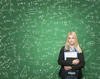 Young girl holding note books, green blackboard with signs at th Royalty Free Stock Photography