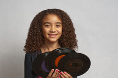 Young girl holding old records. Young mixed race girl with curly hair, smiling, and holding several old 45 rpm records Royalty Free Stock Photo