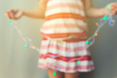 Young girl holding out of focus Christmas lights. Christmas holiday background Stock Photos