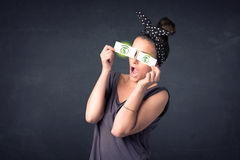 Young girl holding paper with green dollar sign. Concept Royalty Free Stock Images