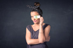 Young girl holding paper with green dollar sign. Concept Stock Image