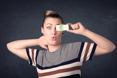 Young girl holding paper with green dollar sign. Concept Stock Photos
