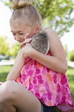 Young girl holding a pet hedgehog outside. In the summer Stock Image