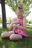 Young girl holding a pet hedgehog outside. In the summer Stock Photos