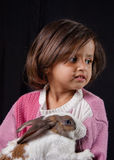 Young girl holding pet rabbit. Young girl in pink sweater holding pet rabbit Stock Images