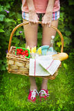 Young girl holding a picnic basket with food Stock Photos