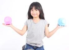 Young girl holding piggy bank Stock Photos